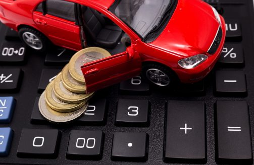 car model and coins on a calculator
