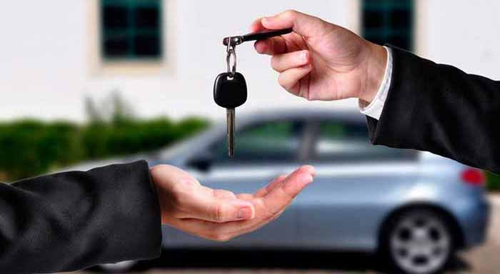 A hand giving a key to another hand. Both persons in suits. Car in the background.